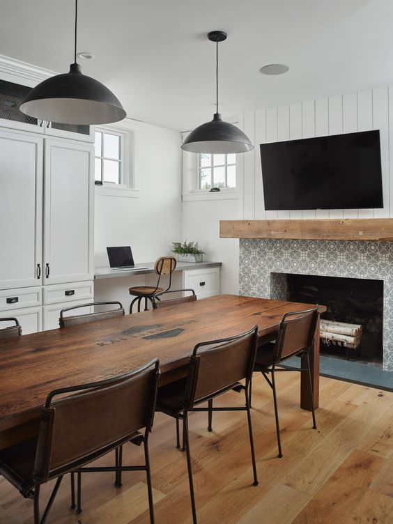 a black and white dining room with white walls, a built-in desk and a storage unit, a fireplace clad with Moroccan tiles, a rich-stained dining table and leather chairs