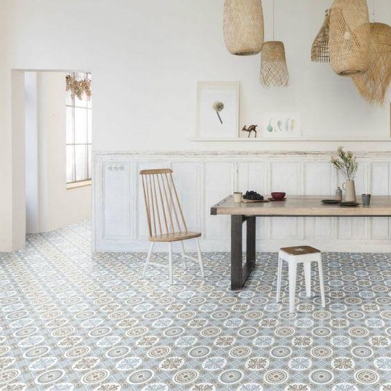 a laid-back dining room with white panels on the walls, a Moroccan tile floor, a dining table, cool chairs and woven pendant lamps