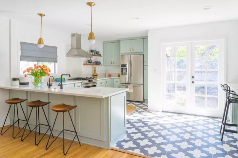 a pretty mint green kitchen with a Moroccan tile floor, brass pendant lamps, woodne stools and black fixtures is a beautiful space