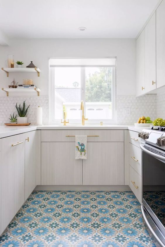 a serene kitchen with whitewashed cabinets, white tiles on the backsplash, colorful Moroccan tiles and gold fixtures
