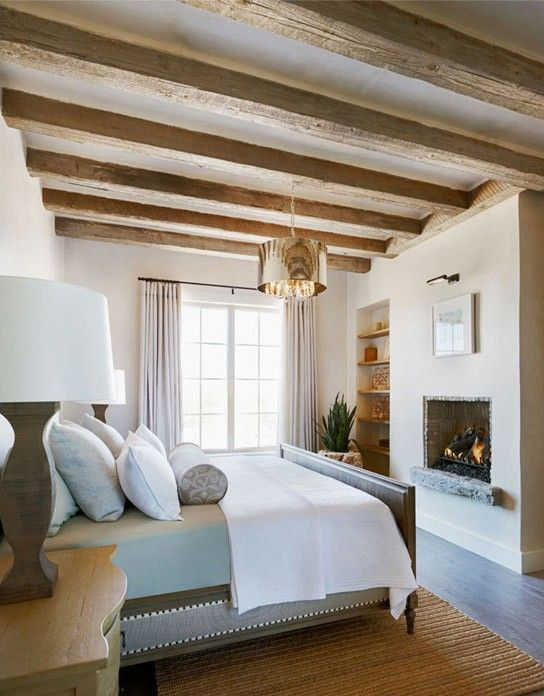 a French farmhouse bedroom with wooden beams, a built-in fireplace, built-in shelves, a neutral bed and bedding, a polished gold lamp
