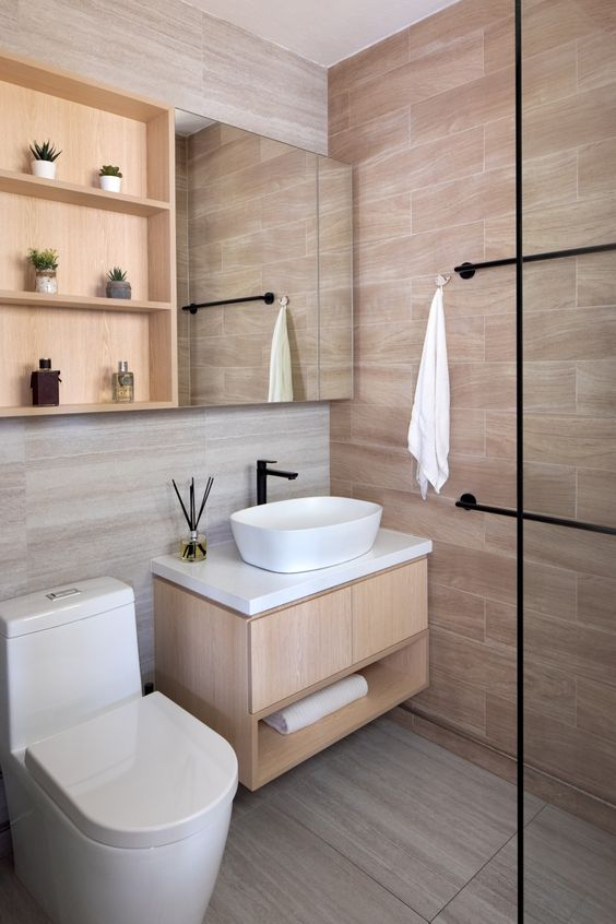 a Japandi bathroom with tan tiles on the walls and floor, a matching vanity and a mirror cabinet plus black fixtures