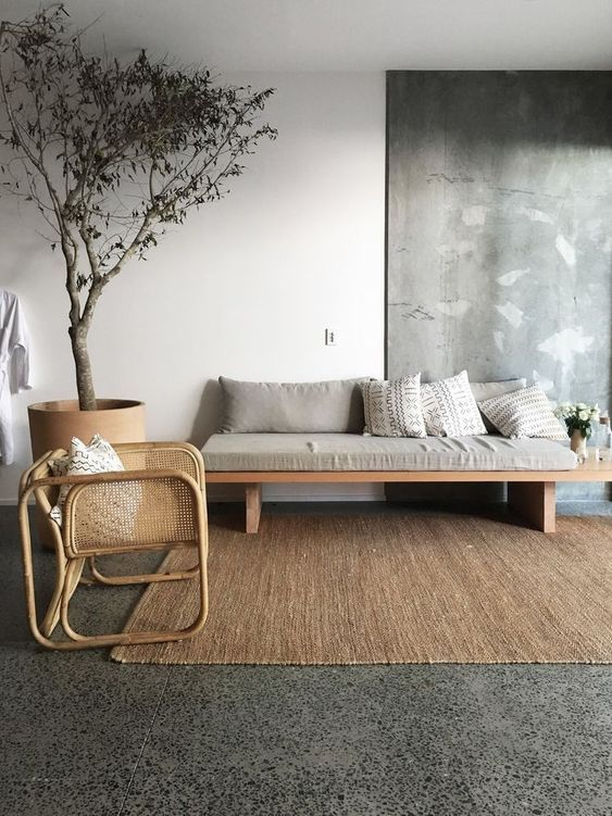a Japandi living room with a grey terrazzo floor, a cool daybed with grey upholstery, a rattan chair, a potted tree and a cool artwork