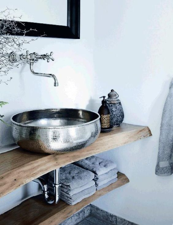a Moroccan bathroom with open living edge shelves, a metal hammered vessl sink, a pot with a lid and grey towels is cool
