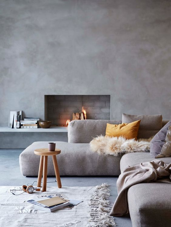 a Scandinavian living room with concrete walls and a floor, a grey sectional with pillows, a wooden stool and some books is cool