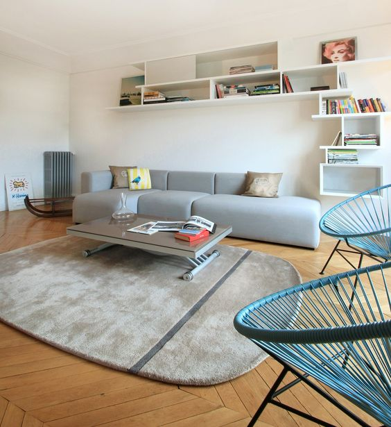 a Scandinavian space wiht a grey low sofa, a grey rug, blue chairs, a low coffee table and a large shelving unit is wow