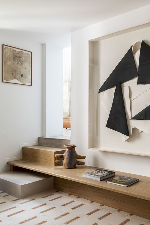 a beautiful Japandi space with a staircase and a bench built into it, a sculptural artwork, a printed rug and an artwork