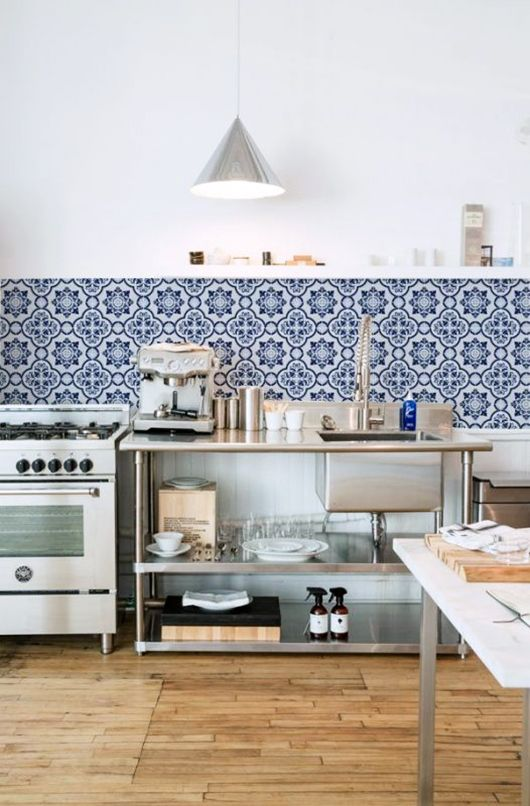 a beautiful and airy industrial kitchen with metal units, a bold blue Moroccan tile backsplash and pendant lamps