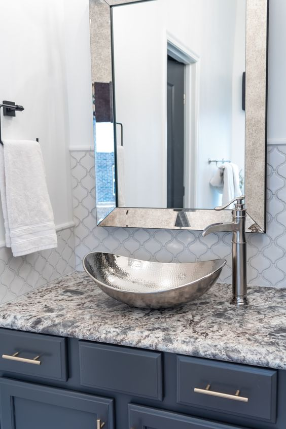 a beautiful bathroom with arabesque tiles, a mirror in a mirror frame, a shiny hammered vessel sink and a blue vanity is chic