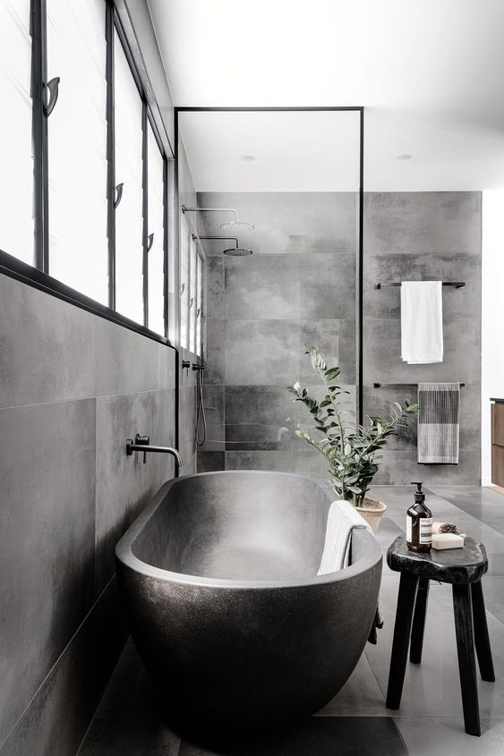 a beautiful contemporary bathroom clad with concrete tiles, with a shower space, a metal bathtub and a black stone stool is gorgeous
