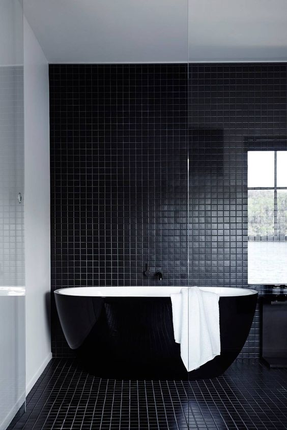 a beautiful contemporary bathroom in black, with small scale tiles, a sleek black bathtub and a black vanity is a lovely idea