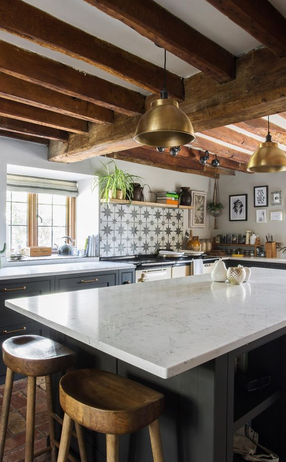 a beautiful farmhouse kitchen with graphite grey cabinets and white stone coutnertops, wooden beams on the ceiling and a star print tile backsplash