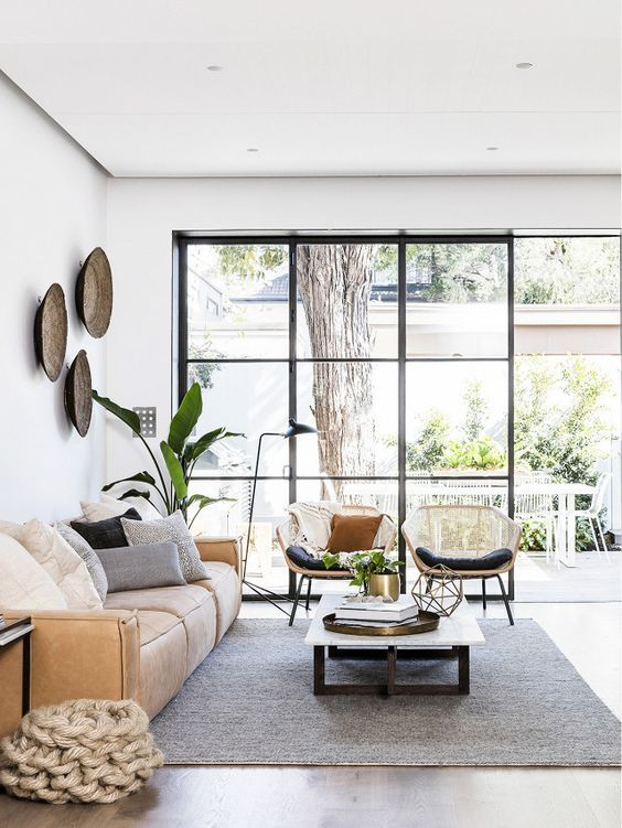 a beautiful living room with a glazed wall, a low leather sofa, a low coffee table, rattan chairs and potted plants