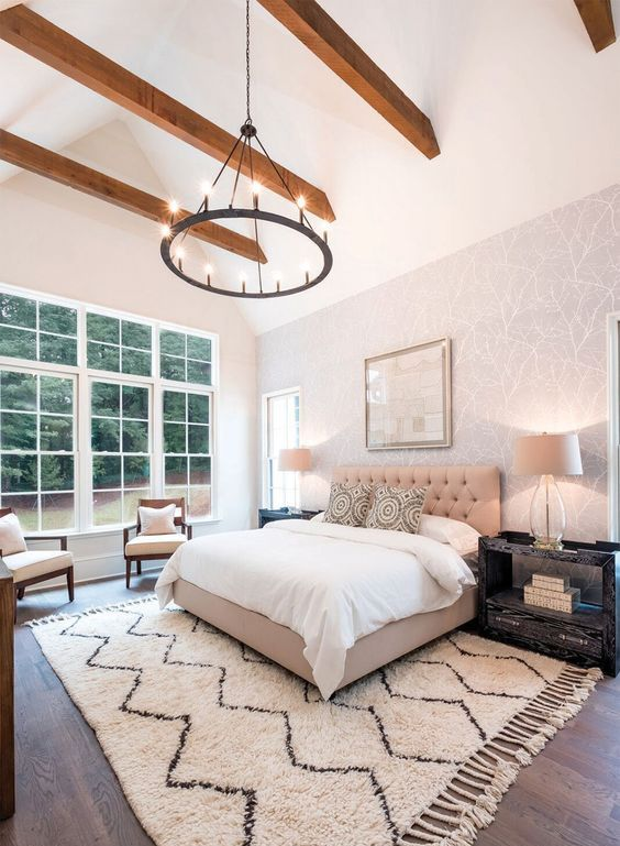 a beautiful modern bedroom with a neutral printed wall, a tan upholstered bed, neutral chairs and black nightstands plus a ceiling with wooden beams
