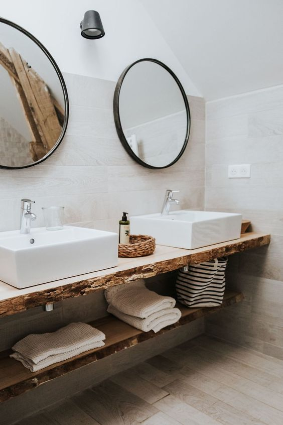 a beautiful organic bathroom covered with wood-looking tiles, a living edge vanity, two square vessel sinks and round mirrors in frames