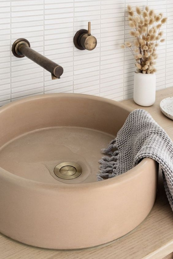 a beautiful tan stone round vessel sink is a refined and chic solution for a contemporary bathroom, with a soft touch of color