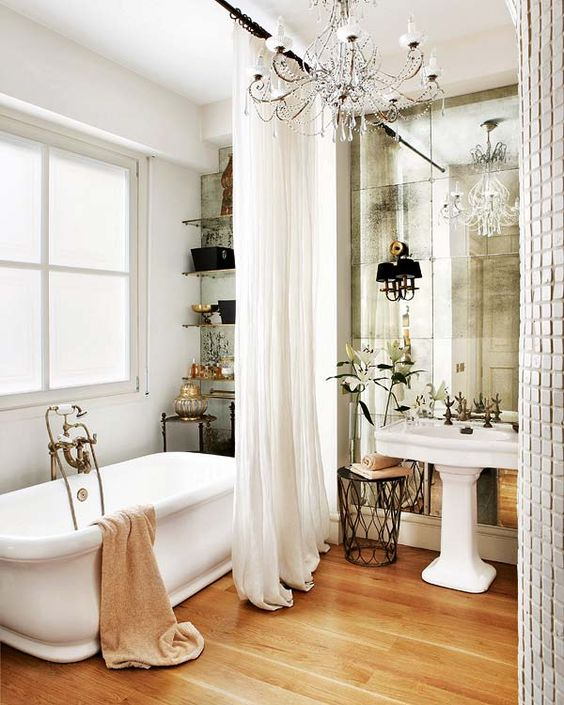 a beautiful vintage bathroom with a pedestal sink, a mirror wall, a crystal chandelier, open shelves and a tub plus a gorgeous curtain is pure chic