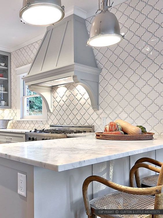a beautiful vintahe dove grey kitchen with glass cabinets, white stone countertops, a vintage greyhood and a wall clad with white arabesque tiles