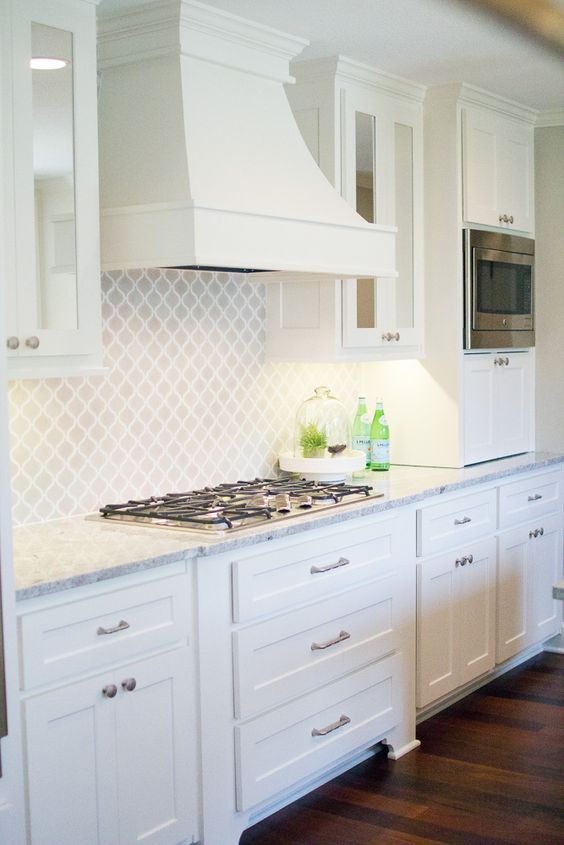 a beautiful white farmhouse kitchen with a matching white arabesque tile backsplash and a vintage hood is a lovely space