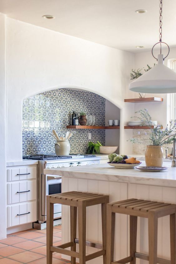 a beautiful white kitchen with planked cabinets, a blue Moroccan tile backsplash, stained stools and pendant lamps is cool