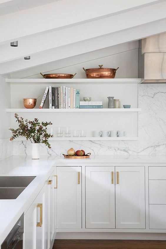 a beautiful white kitchen with shaker cabinets, white countertops and a white stone backsplash, white floating shelves and copper touches
