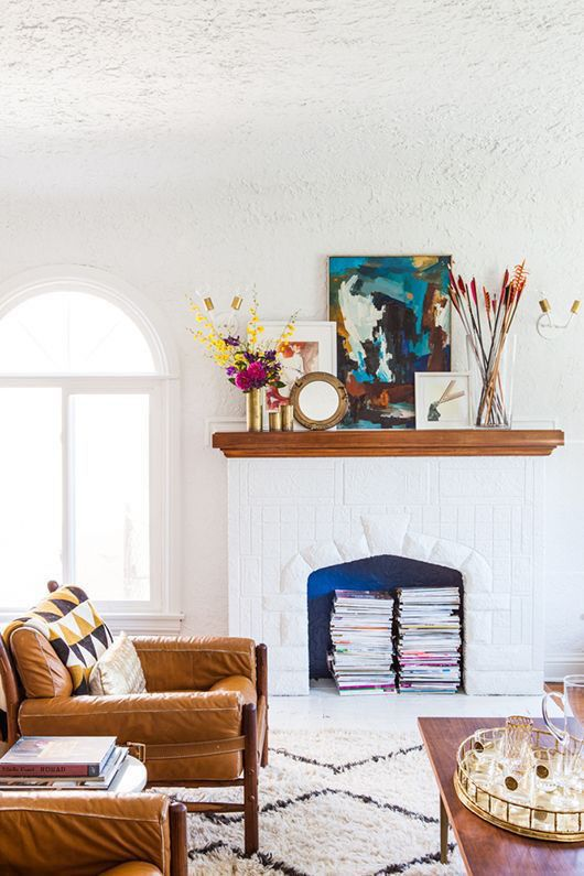 a beautiful white living room with amber leather chairs, a vintage white fireplace used for book storage, with colorful artworks and blooms