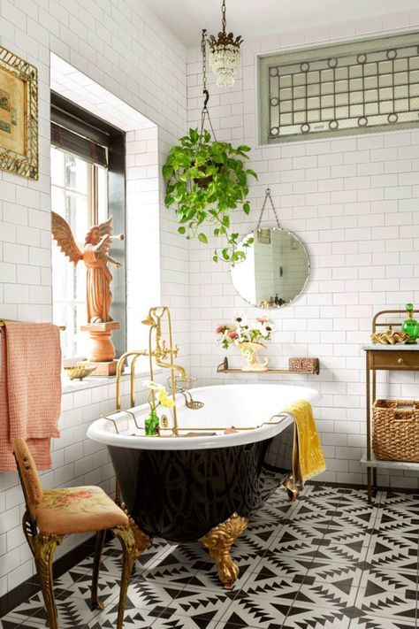 a black and white bathroom with a chic black clawfoot bathtub and bright touches - yellow and pink towels, a vintage chair, statues and potted plants