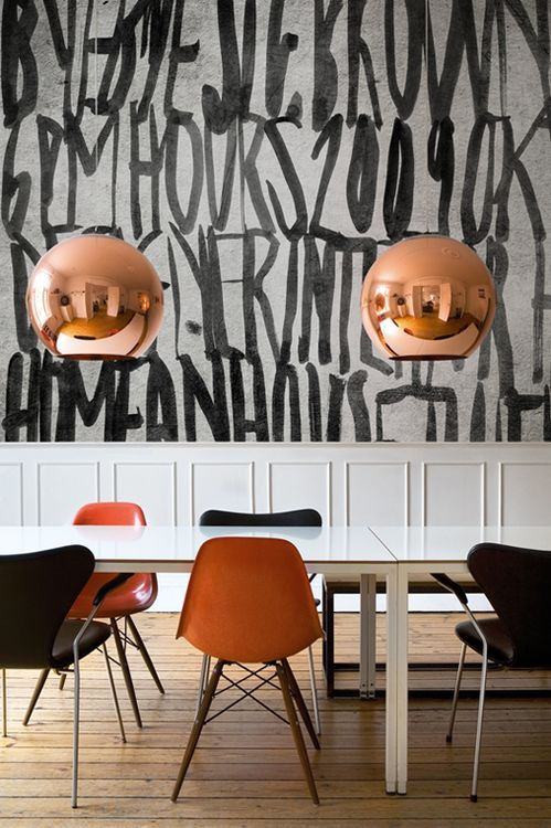 a black and white dining space with amber and black chairs, with copper lamps and a graphic black and white wall