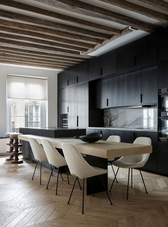 a black contemporary kitchen with a white stone backsplash, a matching kitchen island, a built-in table and wooden beams
