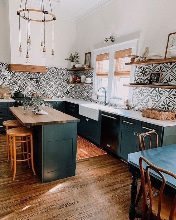 a black farmhouse kitchen with a kitchen island, stained wooden shelves, a bold black and white Moroccan tile backsplash