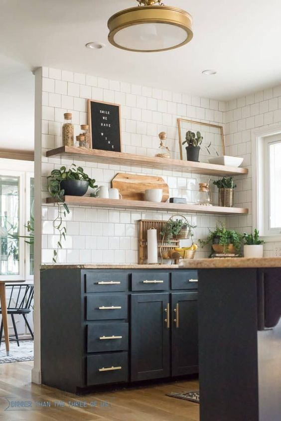 a black farmhouse kitchen with shaker cabinets, butcherblock countertops, floating shelves and potted plants plus gold touches