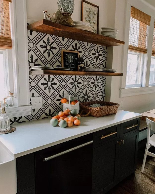 a black farmhouse kitchen with white stone countertops, black and white Moroccan tiles and open shelves is a very chic idea