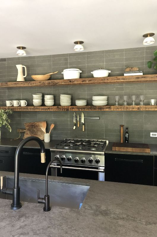 a black kitchen with concrete countertops and a concrete kitchen wall, floating shelves and black fixtures