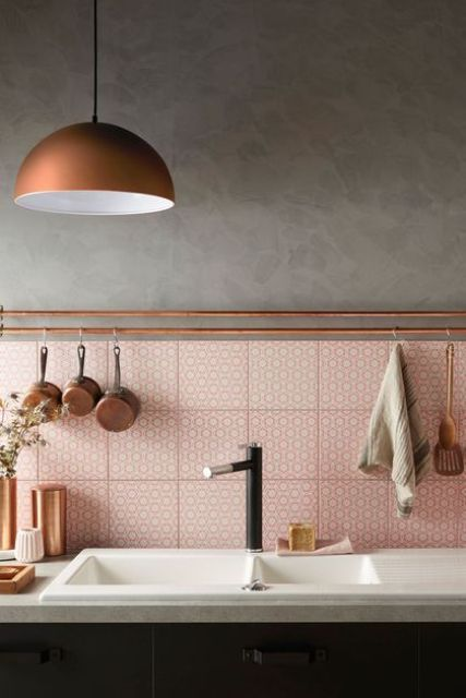 a black kitchen with pink printed tiles on the backsplash, copper holders for various stuff and a copper pendant lamp plus vases for warming up the space