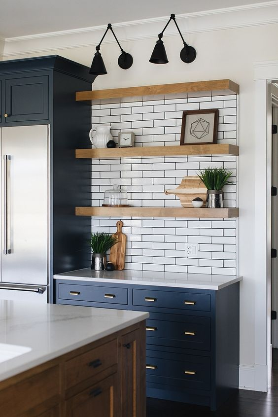 a blue farmhouse kitchen with a white subway tile backsplash and countertops, thick floating shelves and a large stained kitchen island