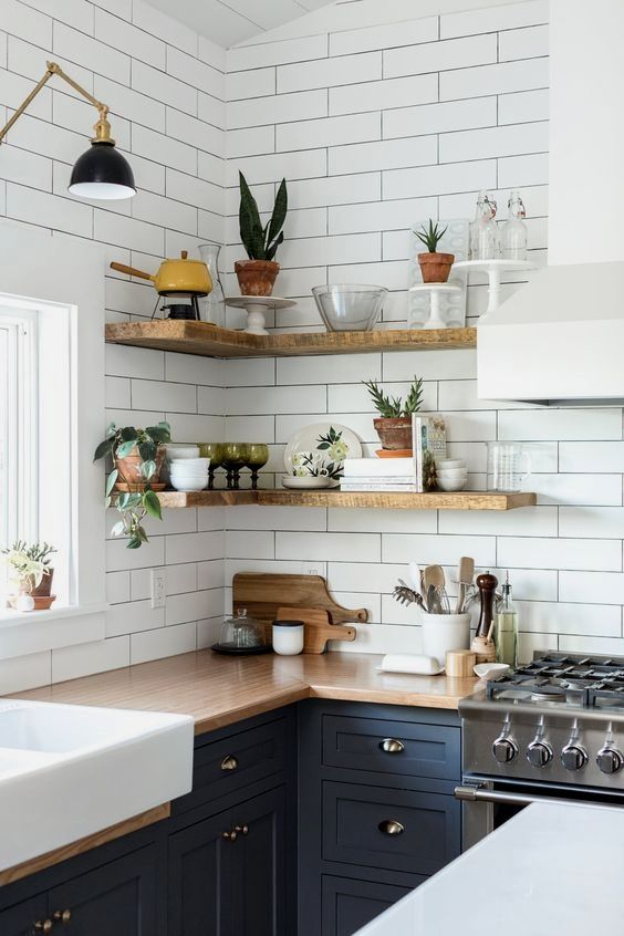 a blue farmhouse kitchen with shaker cabinets, butcherblock countertops, white narrow tiles and light-stained floating corner shelves