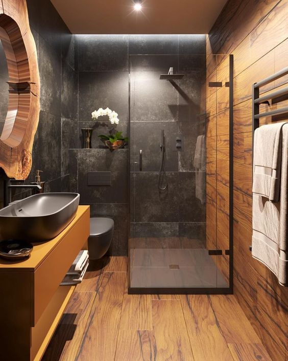 a bold bathroom clad with wood look and black stone tiles, a floating vanity with a black sink, a mirror in a living edge frame and lights