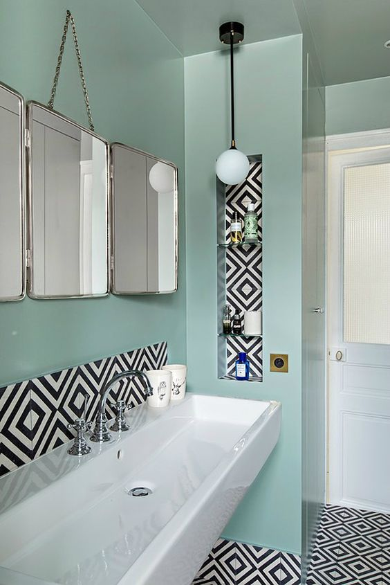 a bold bathroom with mint green walls, bold geo tiles for an accent, a trio of mirrors, pendant lamps and a floating white sink