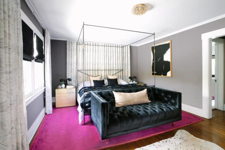 a bold glam bedroom with grey walls, a canopy bed, a black velvet sofa, matching nightstands, a hot pink rug and a statement artwork