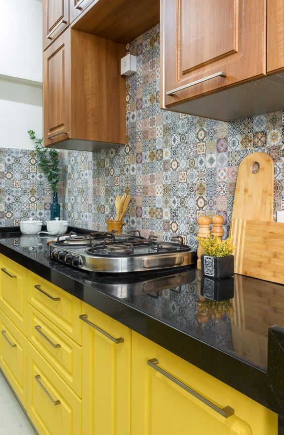 a bold kitchen with yellow and stained cabinets, black countertops, a colorful Moroccan tile backsplash and neutral fixtures
