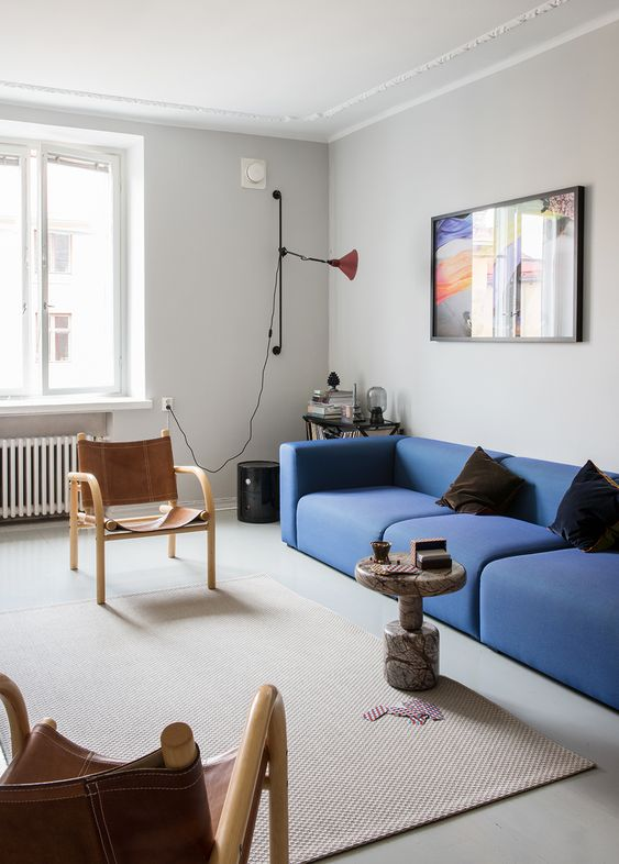 a bold mid-century modern living room with a bright blue low sofa, leather chairs, a stone coffee table and a bright artwork