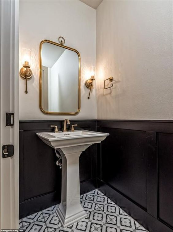 a bold powder room with white walls and black paneling, a pedestal sink, a pattern tile floor and chic brass touches is a gorgeous idea