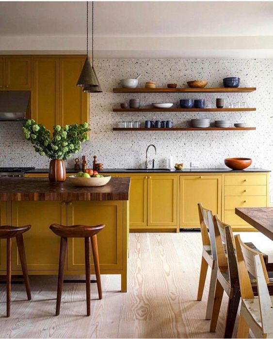 a bold yellow kitchen with shaker cabinets, a large kitchen island, dark countertops, a tile wall and floating shelves