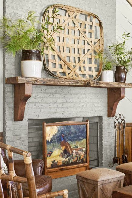 a brick fireplace with a wooden mantel, potted greenery and a basket, a bold woodland-themed artwork on display