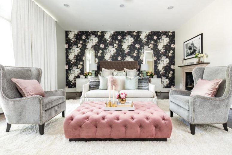 a bright bedroom with a floral accent wall, a taupe upholstered bed, a pink ottoman, grey chairs and mirrors