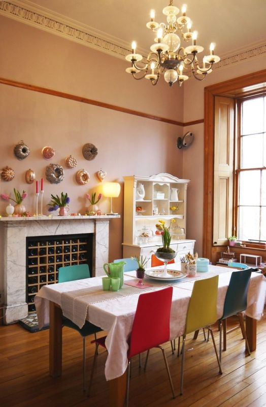 a bright dining room with a built-in fireplace with a marble mantel, a wine bottle storage, colorful candles, bright chairs and a chic chandelier