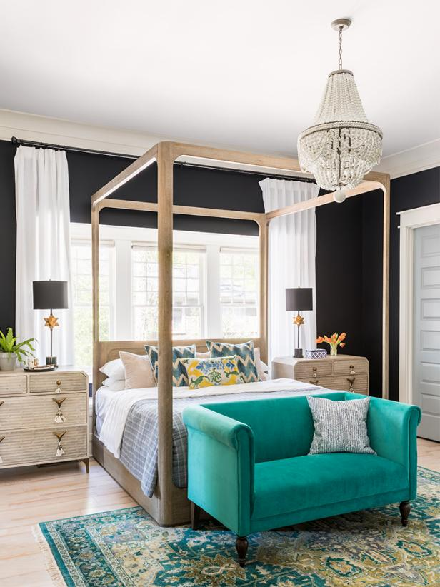 a bright glam bedroom with black walls, a wooden canopy bed, a turquoise loveseat, a beaded chandelier and wooden nightstand