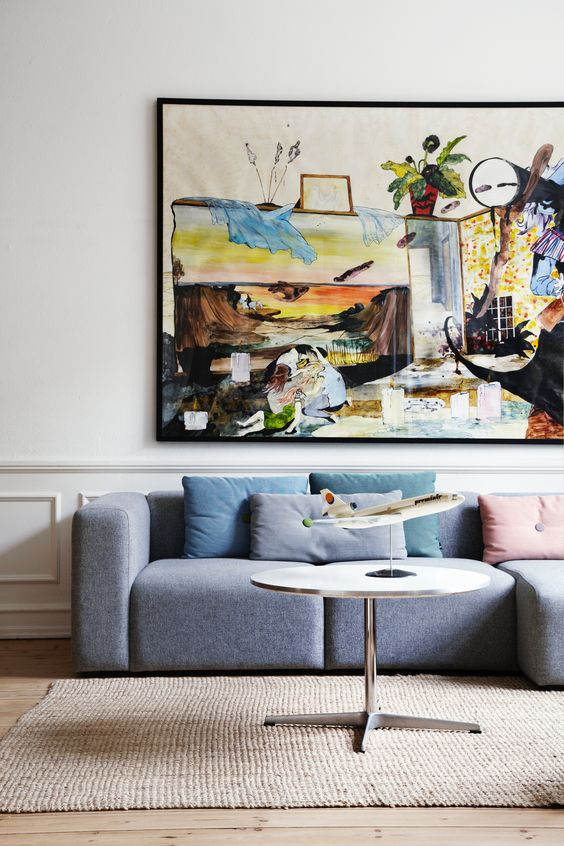 a bright living room with a grey low sofa, a colorful artwork, pastel pillows, a round table is a very cool and bold space