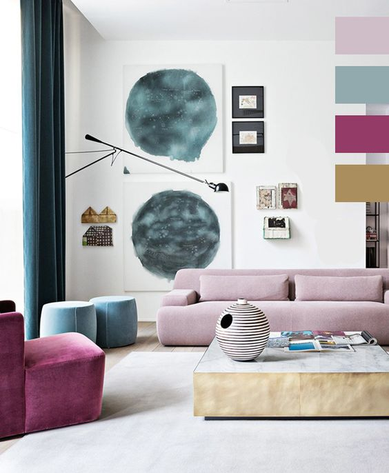 a bright living room with a pale pink low sofa, a purple chair and blue poufs, a watercolor gallery wall and a low coffee table looks cool