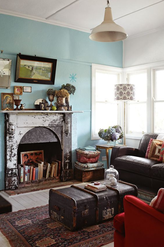 a bright living room with blue walls, a fireplace with a shabby chic mantel, with books, with a chest coffee table and a brown sofa is chic